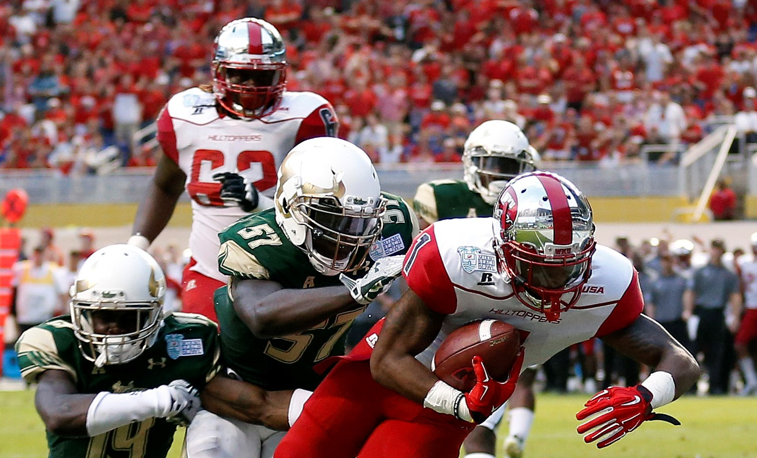 Dec 21, 2015; Miami, FL, USA;Western Kentucky Hilltoppers wide receiver Nacarius Fant (1) scores a touchdown as South Florida Bulls linebacker Nigel Harris (57) and South Florida Bulls cornerback Ronnie Hoggins (19) both make the tackle in the end zone during the second half in the 2015 Miami Beach Bowl at Marlins Park. Mandatory Credit: Steve Mitchell-USA TODAY Sports
