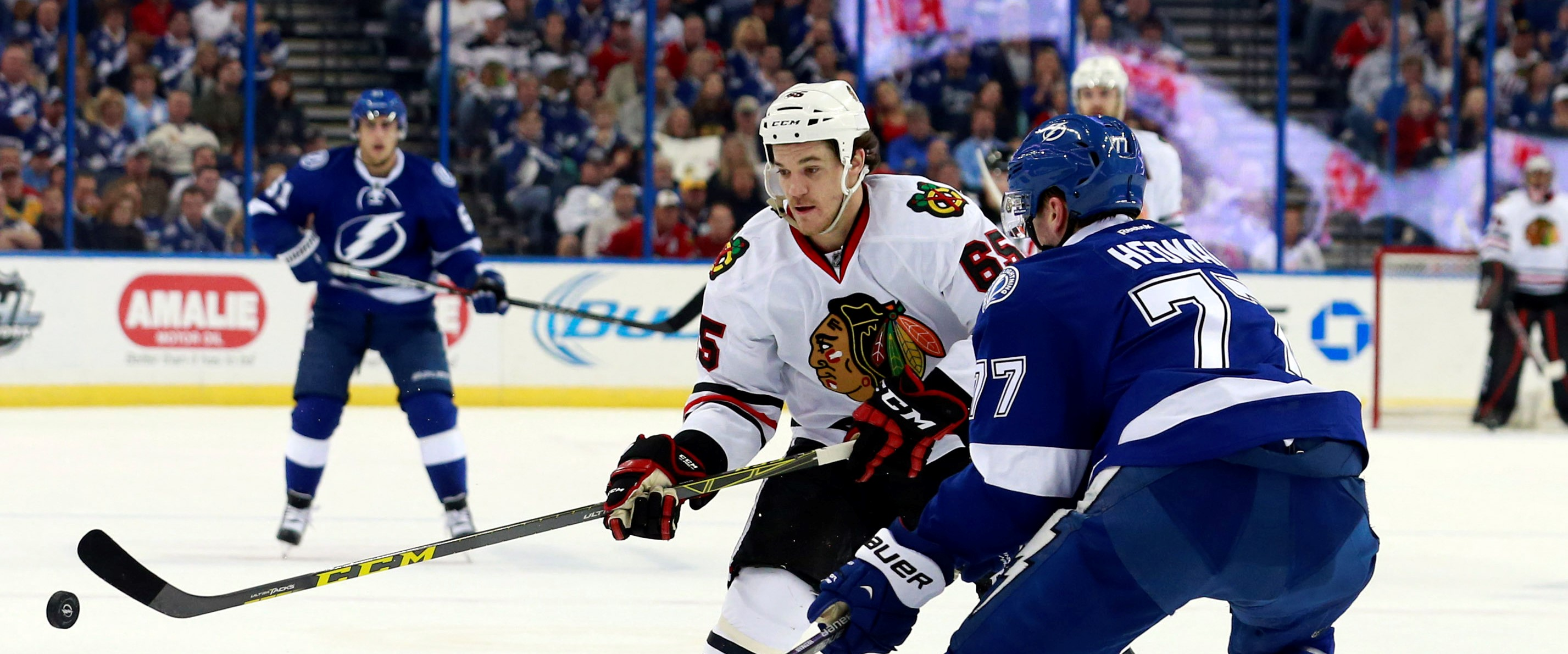 Jan 21, 2016; Tampa, FL, USA; Chicago Blackhawks center Andrew Shaw (65) passes the puck as Tampa Bay Lightning defenseman Victor Hedman (77) defends during the first period at Amalie Arena. Mandatory Credit: Kim Klement-USA TODAY Sports