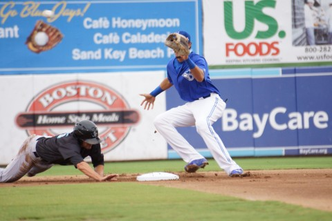 -Dunedin hurler Taylor Cole makes an unsuccessful pick off throw to shortstop Emilio Guerrero in the first inning trying to get Jupiter DH Matt Juengel at second.  Juengel would later score the games first run in the top of the first without the benefit of a hit. (Eddie Michels/Photo)