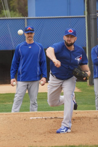 Todd Redmond throws a bull pen session under the watchful eyes of pitching coach Pete Walker (EDDIE MICHELS PHOTO)