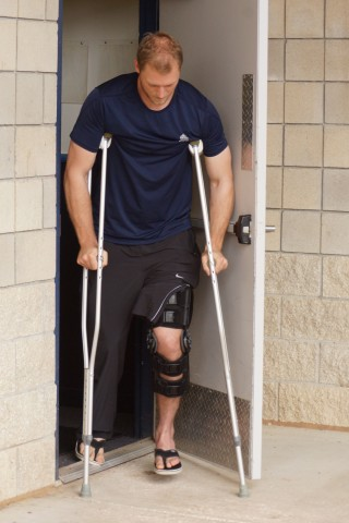 "Michael Saunders looks a bit unsteady as he exits the Blue Jays clubhouse with his new crutches and knee brace.  Saunders tore the meniscus in his left knee on Wednesday when he stepped on a sprinkler head during drills at the team's minor league complex.  ""The sooner the better"", said John Gibbons when ask when Saunders was going to have surgery while Saunders said, ""My goal is to me in a major league game by the all star break.""  Toronto will hold their first full squad workout on Friday. (EDDIE MICHELS/PHOTO)"