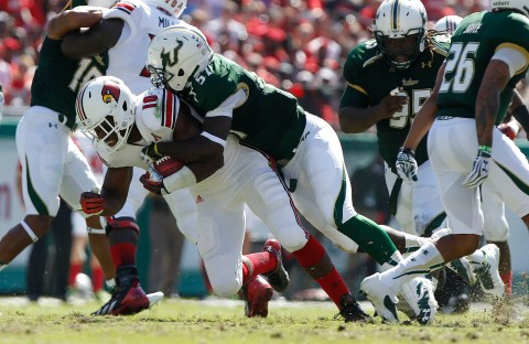 Bulls linebacker Nigel Harris (57) tackles Louisville Cardinals running back Dominique Brown (10) during the first half at Raymond James Stadium. (photo USA TODAY Sports / Kim Klement)