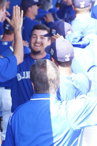 Ceciliani Being Congradulated by Teamates in Dugout (EDDIE MICHELS PHOTO)