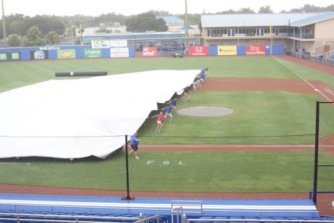 The Dunedin Blue Jays staff pulls the tarp over the infield at Grant Field prior to their game against the Tampa Yankees on Saturday. The start of the game was delayed one hour. (EDDIE MICHELS PHOTO)